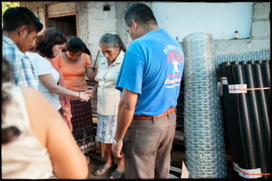 "Members of ""The Village Global"" pray for a widow receiving materials to start a self-sustaining chicken farm."